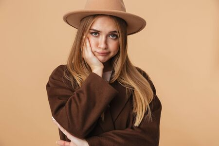 Image of young caucasian girl wearing hat and coat propping up her head with sad look isolated over beige background Banco de Imagens