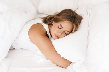 Photo of young caucasian woman with blonde hair sleeping and hugging pillow while lying on bed