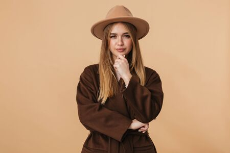 Image of young caucasian girl wearing hat and coat thinking with brooding look isolated over beige background Banco de Imagens