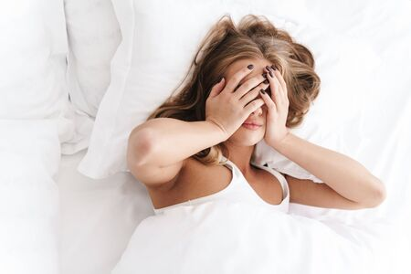 Photo of nice caucasian woman with blonde hair covering her face while lying in bed after sleep