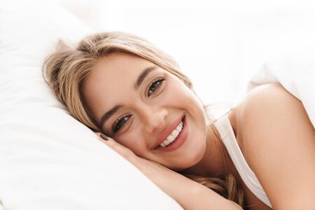 Photo of joyful caucasian woman with blonde hair smiling and looking at camera while lying in bed after sleep
