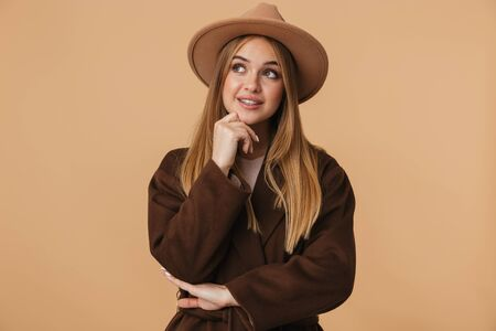 Image of young caucasian girl wearing hat thinking and touching her chin isolated over beige background