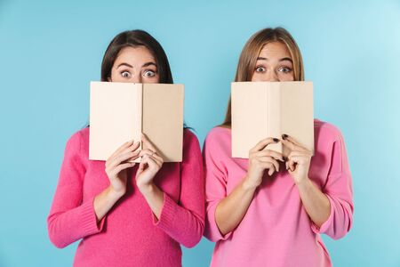 Two lovely young girlfriends standing isolated over blue background, holding books at their faces Фото со стока