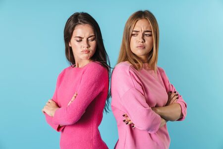 Photo of resentful young women in pink sweaters standing back to back and looking each other isolated over blue background