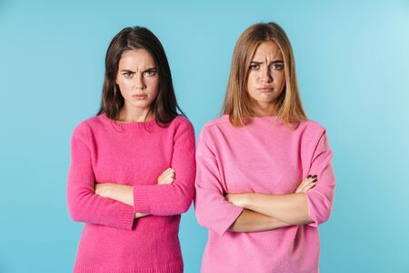 Photo of displeased caucasian women in pink sweaters looking at camera with arms crossed isolated over blue background Фото со стока