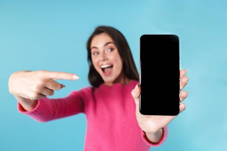 Excited young brunette woman standing isolated over blue background, showing blank screen mobile phone, pointing finger