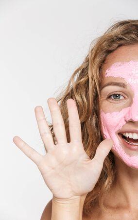 Abgeschnittenes Bild einer fröhlichen Frau mit Gesichtsmaske, die lacht, während sie ihre Handfläche isoliert auf weißem Hintergrund zeigt Standard-Bild