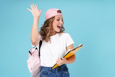 Cheerful cute girl student carrying backpack and holding textbooks while standing isolated over blue background, waving hand