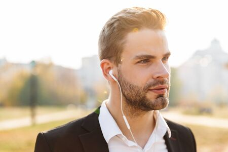 Close up of an attractive young businessman wearing earphones over city background Banque d'images