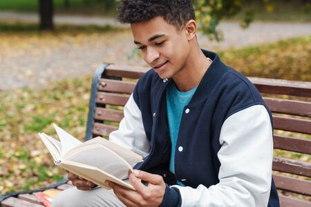 Smiling african boy student sitting on a bench at the park, reading a book