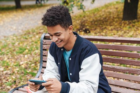 Smiling african boy student sitting on a bench at the park, using mobile phone