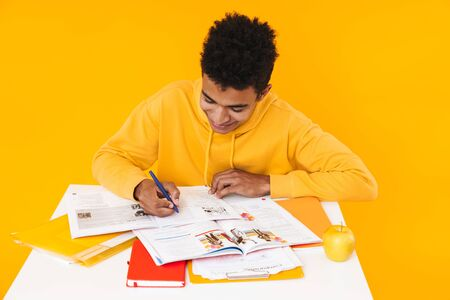 Happy african teenager boy studying while sitting at the desk and writing in textbook isolated over yellow background Zdjęcie Seryjne