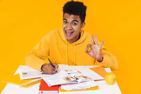 Happy african teenager boy studying while sitting at the desk and writing in textbook isolated over yellow background, showing ok