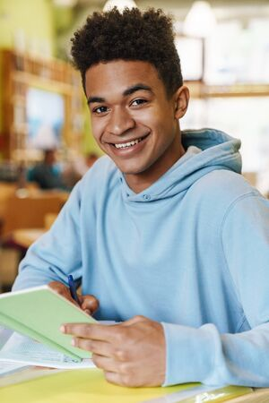 Smiling african boy teenager studying while sitting at the hub indoors