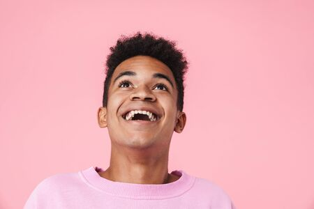 Portrait of a smiling african teenager boy wearing pullower standing isolated over pink background, looking up