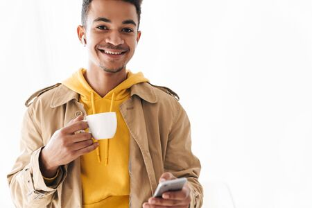 Photo of smiling african american man wearing coat using cellphone and earpod while drinking coffee in white room Stock Photo
