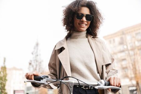 Smiling attractive young african woman wearing autumn coat walking outdoors with bicycle
