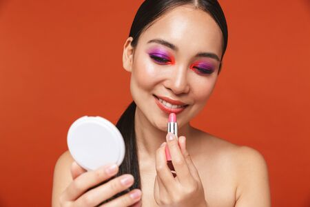 Beauty portrait of an attractive happy young topless asian woman with brunette hair wearing bright makeup, standing isolated over red background, applying lipstick while holding a mirror