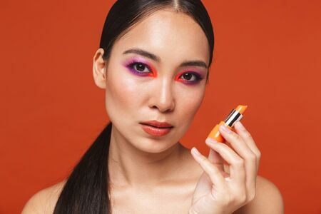 Beauty portrait of an attractive young topless asian woman with brunette hair wearing bright makeup, standing isolated over red background