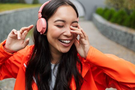 Smiling young asian woman wearing raincoat walking outdoors in the rain, listening to music with wireless headphones