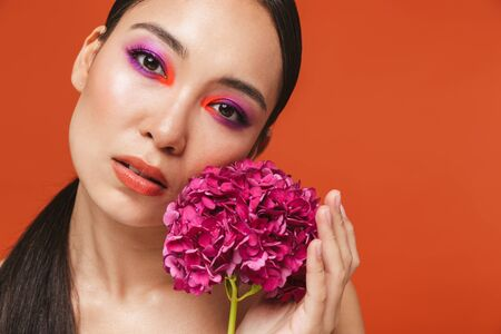 Beauty portrait of an attractive young asian woman with brunette hair wearing bright makeup, standing isolated over red background, posing with a pink flower