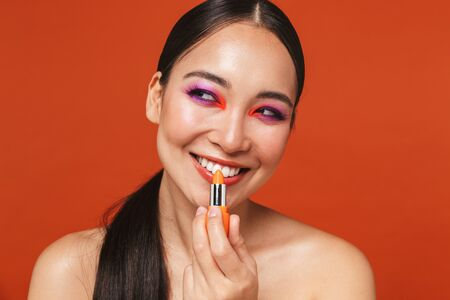 Beauty portrait of an attractive happy young topless asian woman with brunette hair wearing bright makeup, standing isolated over red background, holding a lipstick
