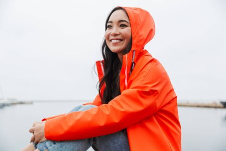 Smiling attractive young asian woman wearing raincoat spending time outdoors walking at the coastland