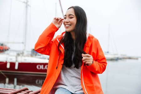 Smiling attractive young asian woman wearing raincoat spending time outdoors walking at the coastland, listening to music with wireless earphones Imagens