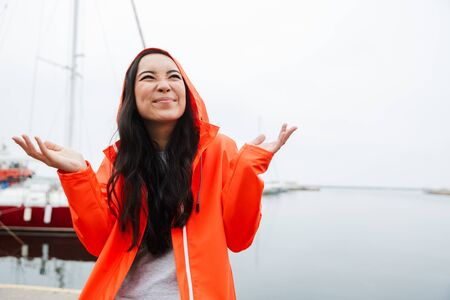 Smiling attractive young asian woman wearing raincoat spending time outdoors walking at the coastland, looking up Imagens