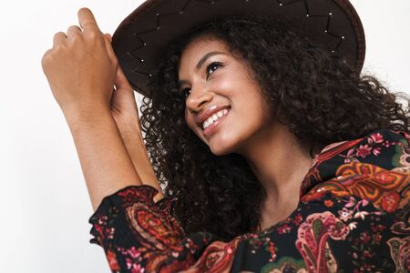 Close up of a beautiful cheerful young woman wearing cowboy hat standing isolated over white background