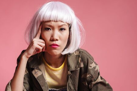 Image of frustrated asian girl wearing white wig thinking and looking at camera isolated over pink background Banco de Imagens