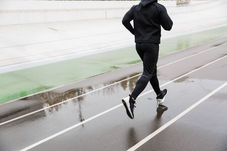 Cropped photo of athletic strong sportsman in tracksuit running while working out on stadium after rain