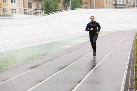 Photo of athletic strong sportsman in tracksuit running while working out on stadium after rain