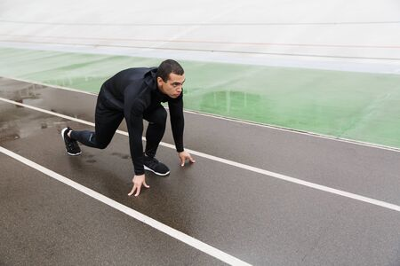 Photo of athletic strong sportsman in tracksuit doing exercise while working out on stadium after rain