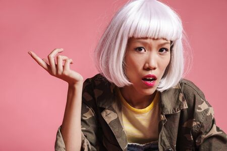 Image of outraged asian girl wearing white wig resenting and gesturing in indignation isolated over pink background Banco de Imagens