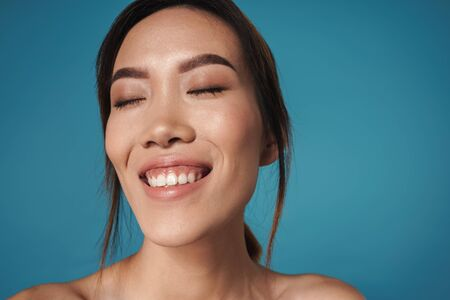 Picture of a beautiful pleased positive smiling asian woman posing isolated over blue wall background. Reklamní fotografie