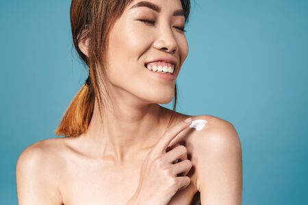 Image of a beautiful asian young cheerful woman posing naked isolated over blue wall background take care of her skin with cream. Stock fotó