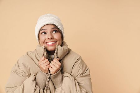 Portrait of funny young woman in winter coat looking aside and smiling isolated over beige background