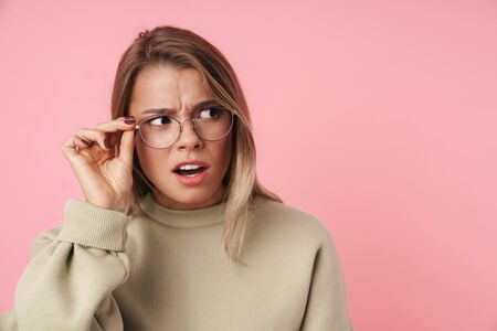 Portrait of young displeased woman in eyeglasses looking aside isolated over pink background