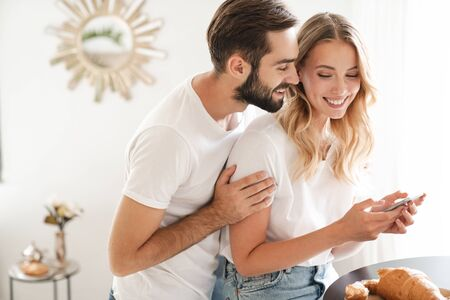 Photo of a smiling loving couple hugging indoors at home using mobile phone. Banque d'images - 140623579
