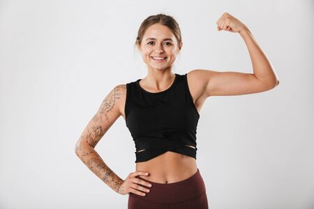 Attractive smiling young fit sportsgirl standing isolated over white background, flexing biceps