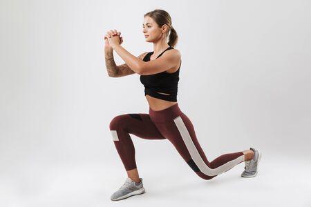 白い背景の上に孤立したワークアウトをしながら、彼女の体を伸ばすスポーツウェアのかわいい女性の写真