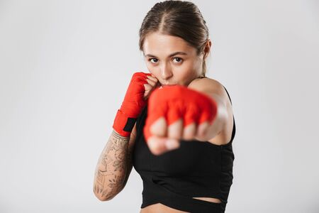Image of focused woman wearing sportswear training in boxing hand wraps isolated over white background