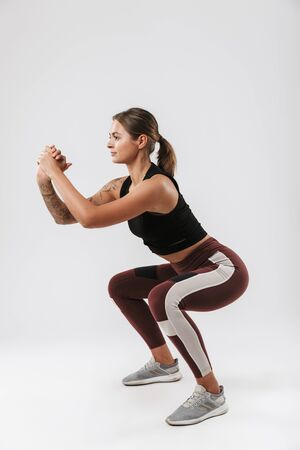 Photo of strong woman in sportswear stretching her body while doing workout isolated over white background