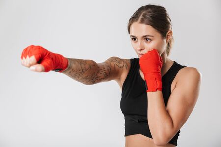 Image of pretty woman wearing sportswear training in boxing hand wraps isolated over white background