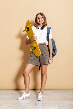 Image of young teen girl wearing headphones smiling and holding skateboard isolated over beige background