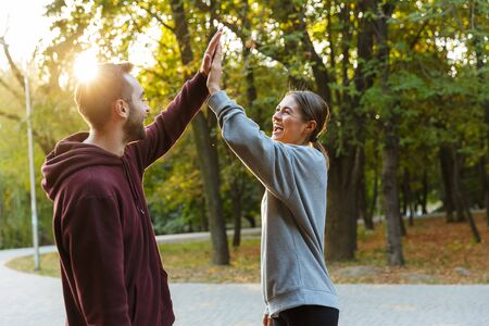 Photo of beautiful delighted couple in sportswear giving five while working out in green park during sunny summer day