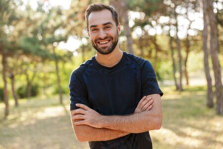Bild eines jungen, starken, fröhlichen, fröhlichen Sportmannes, der draußen im grünen Park der Natur auf der Suche nach Kamera posiert.