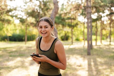 Photo of happy nice woman in sportswear using cellphone and laughing while working out in sunny green park