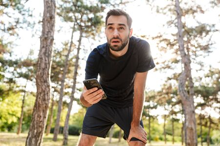 Photo of young tired man in sportswear using cellphone while working out in sunny green park